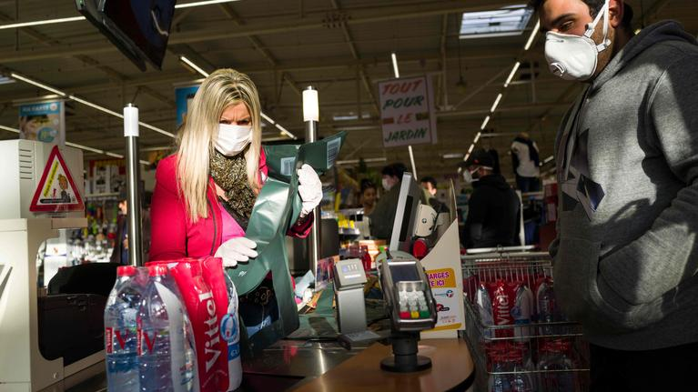 A cashier works wearing a face mask in a supermarket on March 16, 2020, in Pfastatt, eastern France, as people stock up on goods amid the outbreak of COVID-19, caused by the novel coronavirus. - The French president is due to address the nation on the evening of March 16, with many expecting him to unveil more strict home confinement rules in a bid to prevent the virus from spreading. France has closed down all schools, theatres, cinemas and a range of shops, with only those selling food and other essential items allowed to remain open. The balance sheet of the epidemic climbed to 127 dead and 5,423 confirmed cases in France. (Photo by SEBASTIEN BOZON / AFP)